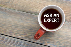 Ask an expert. Coffee cup with message. Office desk table top view. Ask an expert. Coffee cup with message. Office desk table top view Royalty Free Stock Photography