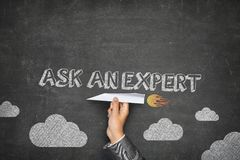 Ask an expert concept. On black blackboard with businessman hand holding paper plane Royalty Free Stock Image