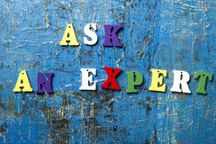 Ask an EXPERT concept. Wooden colorful abc letter on abstract blue grunge background. Stock Image