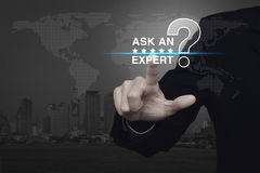 Ask an expert, Elements of this image furnished by NASA. Businessman pressing ask an expert with star and question mark sign icon over black and white world map royalty free stock images