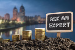 Ask an expert. Financial opportunity concept. Golden coins in soil Chalkboard on blurred urban background Stock Images