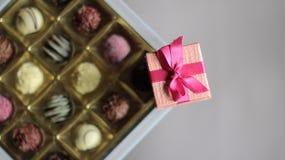Ask för ask för chokladgodis och rosa färgsmycken Arkivbilder