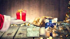 Ask för gåva för jul för Santa Claus hand hållande över träbakgrund Royaltyfri Fotografi