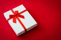 Ask för gåva för San valentin vit på röd bakgrund Fotografering för Bildbyråer