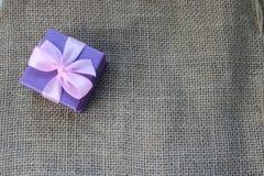 Ask för gåva för härlig festlig papp för gåva liten med en rosa pilbåge på en bakgrund av brun linne, själv-gjord unbleached tork arkivbild