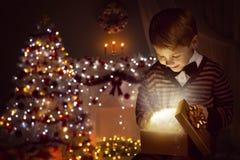 Ask för gåva för julbarn öppen närvarande, lycklig unge som öppnar Giftbox fotografering för bildbyråer