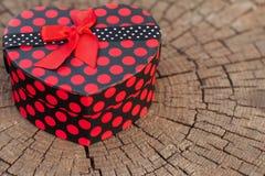 Ask för hjärtaShape gåva på trädstammen Arkivfoto