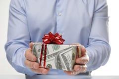 Ask för maninnehavgåva som slås in i dekorativt papper med dollarmodellen på vit bakgrund royaltyfri bild