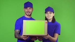 Ask för packe för två lyckliga yrkesmässiga leveransarbetare hållande ut till kameran lager videofilmer