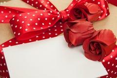 Ask för röda rosor, kort- och gåva Valentinbakgrund som hälsar bilen Royaltyfria Foton