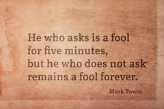 Ask fool Twain. He who asks is a fool for five minutes - famous American writer Mark Twain quote printed on vintage grunge paper royalty free stock image