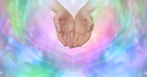 Ask and it is Given. Female cupped hands emerging from a wispy pastel colored background with plenty of copy space ideal for a fundraising campaign Royalty Free Stock Photography