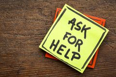 Ask for help advice or reminder. Handwriting on a sticky note against rustic wood Stock Photo