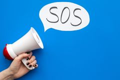 Ask for help concept. Megaphone near cloud with word SOS on blue background top view copy space. Ask for help concept. Megaphone near cloud with word SOS on blue royalty free stock photos