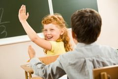 Ask me. Photo of happy schoolgirl sitting and raising her hand at the lesson Stock Images