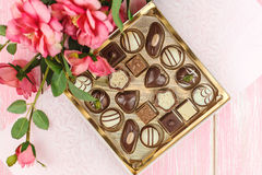 Ask med choklader och rosa färgblommor selektivt Arkivbilder