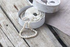 Ask med den pärlemorfärg halsbandet och broschen arkivbilder