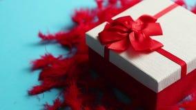 Ask med en gåva som binds med ett band som förläggas på röda fjädrar
