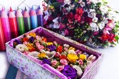 Ask med macarons och blommor royaltyfria foton