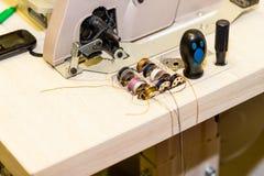 Ask med metallrullar av kulöra trådar nära symaskinen Skräddarebranschbegrepp märkes- atelier som anpassar arkivbild