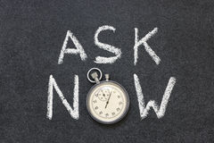 Ask now. Phrase handwritten on chalkboard with vintage precise stopwatch used instead of O Stock Images