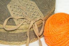 Ask som täckas med tyg, och en boll av orange garn royaltyfria foton