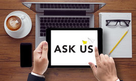 Ask us concept. On the tablet pc screen held by businessman hands - online, top view Royalty Free Stock Images