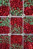 Askar av jordgubbar på skärm på en gatastall arkivbild