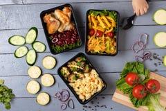 Askar för matbehållare och flickahanden rymmer skeden, rå grönsaker, zuchinien och aubergine, moroten och löken, stället för text royaltyfri bild
