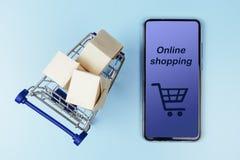 Askar i en shoppa vagn och en smartphone på blå bakgrund Top beskådar arkivbild