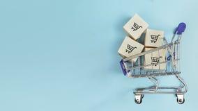Askar i en shoppa vagn på blå bakgrund Begrepp: online-shopping, e-kommers och leverans av gods kopiera avstånd royaltyfri fotografi