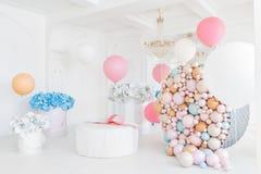 Askar med blommor och en stor pudrinitsa med bollar och ballonger i rum dekorerade för födelsedagparti Arkivfoton