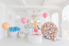 Askar med blommor och en stor pudrinitsa med bollar och ballonger i rum dekorerade för födelsedagparti Arkivbild
