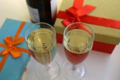 Askar med gåvor och exponeringsglas av champagne royaltyfri fotografi