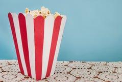 Asken av popcorn på blå bakgrund och snör åt doilyen med utrymme för text royaltyfri foto