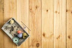 Asken av skräddaren, scissor, måttband- och sömnadtrådar med färgrika spolar för patchwork på träbakgrund Royaltyfria Bilder
