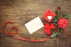 Asken för valentindaggåvan som var röd på träkort, steg pilbågen för blomma- och gåvaaskbandet - kuvertförälskelsepost Valentine  arkivbild