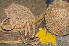 Asken som täckas med tyg, och en boll av tvinnar med lönnlövet Arkivfoton