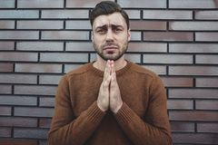Asking for forgiveness .Religion concept. Caucasian young man praying against the gray brick wall royalty free stock photography