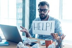 Asking for help. Frustrated young beard man holding piece of paper and asking for help while sitting at his working place in office Royalty Free Stock Photos