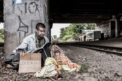 """Asking for job. Homeless woman with sign """"I need job"""" sitting under the bridge  and reading magazine Royalty Free Stock Photos"""