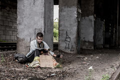 """Asking for job. Homeless woman with sign """"I need job"""" sitting under the bridge  and reading magazine Stock Photography"""