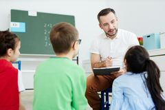 Asking kids. Contemporary teacher pointing at one of kids while listening to their answers royalty free stock photo