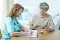 Asking about new drugs. Old women is asking her trusted doctor about new drugs Stock Photography