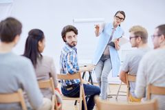 Asking question. Confident young teacher pointing at one of attendants while asking question at conference stock photo