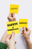 Asking for Safety. Hands raising yellow SAFETY notes Stock Photos