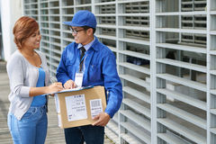 Asking for signature. Cheerful courier asking for signature for the delivery Royalty Free Stock Images