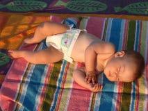 Asleep. Baby sleeping on a beach Royalty Free Stock Photos