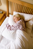 Asleep. A young woman in pyjamas asleep in bed Royalty Free Stock Images