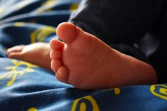 Barefooted sleeping baby on blue sheet with yellow suns royalty free stock image
